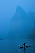 Silhouette eines Kormoranfischers und Vögel auf einem mit Laternen beleuchteten Floß in der Morgendämmerung auf dem Li-Fluss mit fernen Bergen, China, Asien