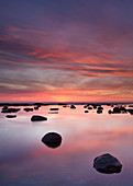 Boulders and reflections in the sea at sunrise, Saltwick Bay, Yorkshire, England, United Kingdom, Europe