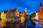 The Belfry and buildings lit up at night along a Canal in the historic center of Bruges, UNESCO World Heritage Site, Belgium, Europe