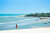 Eine junge Frau entlang des Strandes in Jericoacoara, Ceara, Brasilien, Südamerika