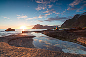 Pink clouds and midnight sun are reflected in the blue sea framed by rocky peaks, Uttakleiv, Lofoten Islands, Norway, Scandinavia, Europe