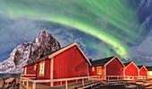 The green light of the Northern Lights (aurora borealis) lights up fishermans cabins, Hamnoy, Lofoten Islands, Arctic, Norway, Scandinavia, Europe
