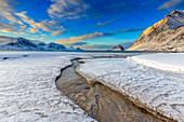 Der goldene Sonnenaufgang spiegelte sich in einem klaren Meeresstrom in dem der Schnee geschmolzen ist, Haukland, Lofoten, Arktis, Norwegen, Skandinavien, Europa