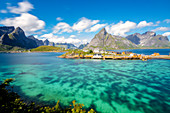 Das türkisfarbene Meer um das typische Fischerdorf, umgeben von felsigen Gipfeln, Sakrisoy, Reine, Moskenesoya, Lofoten, Norwegen, Skandinavien, Europa