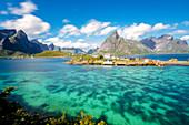 The turquoise sea frames the typical fishing village surrounded by rocky peaks, Sakrisoy, Reine, Moskenesoya, Lofoten Islands, Norway, Scandinavia, Europe