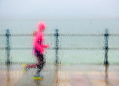 runner braving the elements on a winter seafront run, West Kirkby, Wirral, England, United Kingdom, Europe