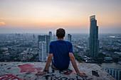 Mann beobachtet den Sonnenuntergang über der Skyline der Stadt, Bangkok, Thailand, Südostasien, Asien beobachtet