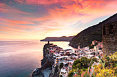 The setting sun lights up the sky and casts an orange glow over the old town and harbour of Vernazza, Cinque Terre, UNESCO World Heritage Site, Liguria, Italy, Europe