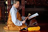 Buddhistische Zeremonie im Tempel, Mönch spielt auf einem Holzfisch (Schlaginstrument), Ho-Chi-Minh-Stadt, Vietnam, Indochina, Südostasien, Asien