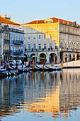 Festgebundene Moliceiros entlang des Hauptkanals bei Sonnenuntergang, Aveiro, 'Venedig Portugals', Beira Littoral, Portugal, Europa