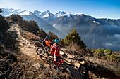 Mountainbiker machen eine Pause auf einem einspurigen Enduro-Weg im nepalesischen Himalaya in der Nähe der Region Langtang, Nepal, Asien