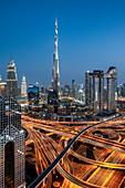 Burj Khalifa at sunset with the Dusit Thani hotel and The Address near the huge intersection of Sheikh Zayed Road, Dubai, United Arab Emirates, Middle East