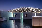 The Louvre Abu Dhabi Museum and Art Gallery at sunset with all the roof lights lit on Saadiyat Island in Abu Dhabi, United Arab Emirates, Middle East