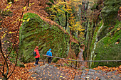 Man and woman hiking in the Elbe Sandstone Mountains, Kuhstall, Kirnitzschtal, Elbsandsteingebirge, Saxon Switzerland National Park, Saxon Switzerland, Saxony, Germany
