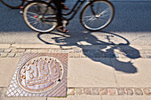 Canal hatch with Copenhagen's crest, pavement, shadow of a biker. Bredgade street, Copenhagen, Zealand, Denmark