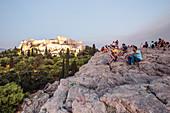 Besucher am Areopag, Marshügel, genießen die Abendstimmung und den Blick zur Akropolis, Athen, Griechenland