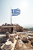 Visitors under the Greek flag on the Acropolis, Athens, Greece