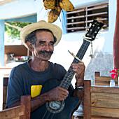 Cuban man with guitar in a retaurant in Trinidad