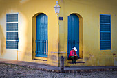 Man with hat having siesta on the street in Trinidad, Cuba