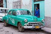 Mechanic with green classic car in Havana, Cuba
