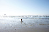 Child in a hat runs into the water on Big Sur beach. California, United States