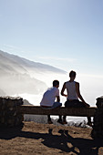 Young couple looks at coastal panorama in the fog. Highway 1, California, USA
