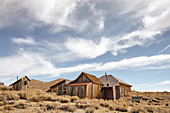 Buildings in the ghost town of Bodie under a cloudy sky in the Eastern Sierra, California, USA.