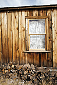 House side with window and firewood in the ghost town Bodie. Eastern Sierra, California, United States.