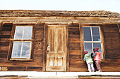 Children look through a window into a house in the ghost town of Bodie. Eastern Sierra, California, United States.