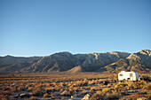 Caravan in steppe landscape in front of the White Mountains, Eastern Sierra, California, USA.