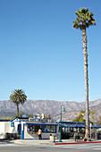 Burger restaurant with palm trees against mountains and blue sky, Carpinteria, California, USA