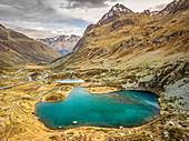 Türkis schimmernder Bergsee in einer kargen Landschaft auf dem Julierpass, Graubünden, Schweiz, Europa