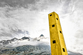 Yellow Origen Tower looms in the sky with mountains in the background. Julier Pass, Graubünden, Switzerland, Europe