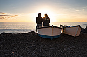 Two women sit on a boat and look out over the Atlantic, El Remo, La Palma, Canary Islands, Spain, Europe