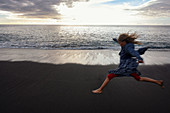 Jumping girl on El Remo beach, La Palma, Canary Islands, Spain, Europe
