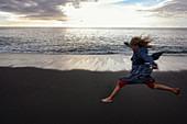 Jumping girl on El Remo beach, La Palma, Canary Islands, Spain, Europe