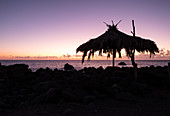 Palm umbrella with a view of the Atlantic Ocean at sunset in La Bombilla, La Palma, Canary Islands, Spain, Europe