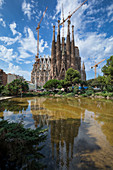 Kathedrale von Gaudi Sagrada Familia von außen mit Spiegelung im Wasser bei Sonne, Barcelona, Spanien\n