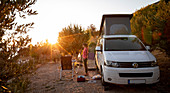 Woman stands in front of white campervan VW bus with backlight at sunset, Brac Croatia