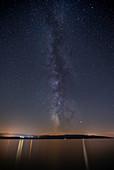 Milky Way in the night sky over the sea on the island of Brac with footbridge, Croatia