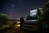 Kissing couple in front of campervan VW bus at night under Milky Way, Brac Croatia