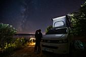 Kissing couple in front of campervan VW bus at night under Milky Way, Brac Croatia