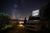 Mann am Campervan VW Bus bei Nacht mit Blick zur Milchstraße, Brac, Kroatien