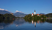 Wallfahrtskirche Mariä Himmelfahrt auf Insel im Bleder See mit blauem Himmel und Spiegelung, Bled Slowenien\n