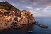 Bucht in Cinque Terre mit Dorf Manarola im Sonnenuntergang, Italien\n
