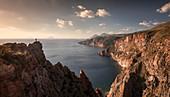Man on cliff on Lipari rocky coast at sunset, Sicily Italy