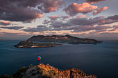 Man with red jacket on coast of Lipari with view of Vulcano volcanic island in sunset, Sicily Italy