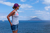 Woman on Panarea looking towards Stromboli, Sicily Italy