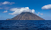 Stromboli volcanic island in the sea with clouds at the summit at sun, Sicily Italy