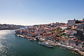 Cityscape of Porto on the Douro River by day with sun, Portugal